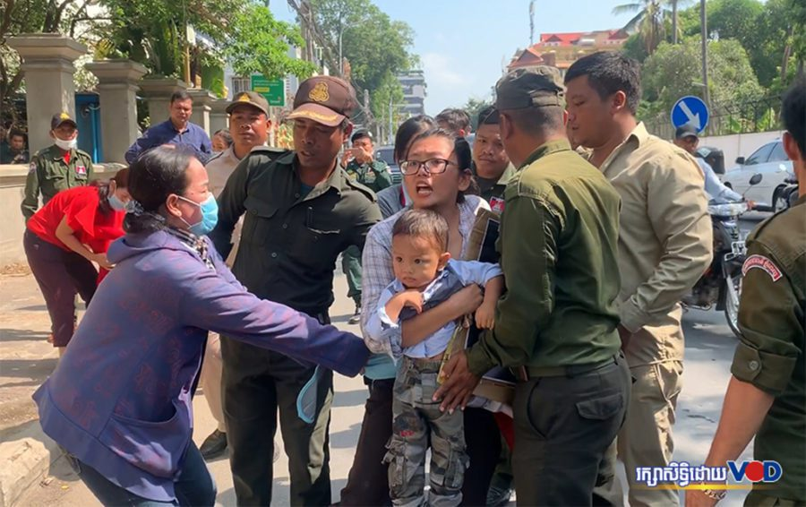 Long Kimheang, the wife of imprisoned translator Rath Rott Mony, holds her son as she is dragged by masked women and authorities while protesting in front of the Russian Embassy in Phnom Penh on April 3, 2019. (Hy Chhay/VOD)