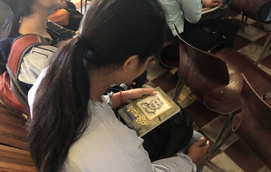 "A woman holds a copy of Sovicheth Meta's Khmer translation of Hédi Fried's book ""Questions I Am Asked About the Holocaust"" in Phnom Penh on July 19, 2019. (Matt Surrusco)"