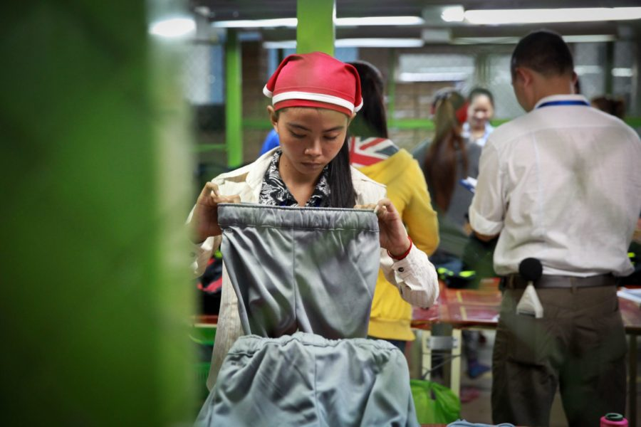 A garment worker checks pants in a factory in Cambodia on December 9, 2014 (ILO)
