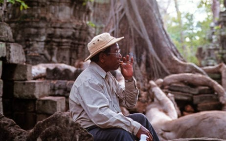 Musician Yoeun Mek smokes a cigarette at the Angkor Archaeological Park in April 1999. (Alan Morgan/Creative Commons)