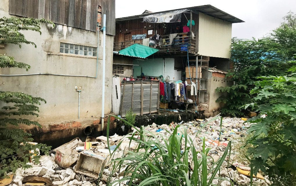 Trash floats on a canal outside houses in Tuol Sangkae commune in Phnom Penh's Russei Keo district, on September 18, 2019. (Chhorn Sopheap)