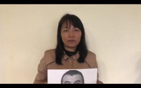 Grace Karaca holds up a photo of her arrested husband, Osman Karaca, in a video she posted to Twitter on October 18, 2019.