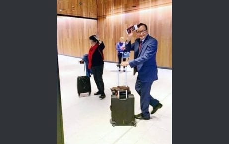 Sam Rainsy walks with his wife Tioulong Saumura while holding a suitcase and his passport, in this photograph posted to Sam Rainsy's Facebook page.