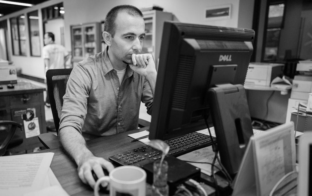 Zsombor Peter, a former Cambodia Daily associate editor, works at his computer in the newsroom in Phnom Penh on September 3, 2017, when staff produced the final issue of the newspaper. (Ben Woods)