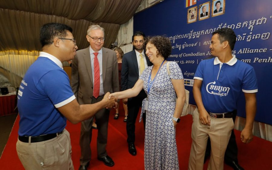 Swedish Ambassador Bjorn Haggmark (second left) looks on as Nop Vy, CamboJA's director (left), shakes hands with EU Ambassador Carmen Moreno at the CamboJA launch event on December 13, 2019 in Phnom Penh. (CamboJA)