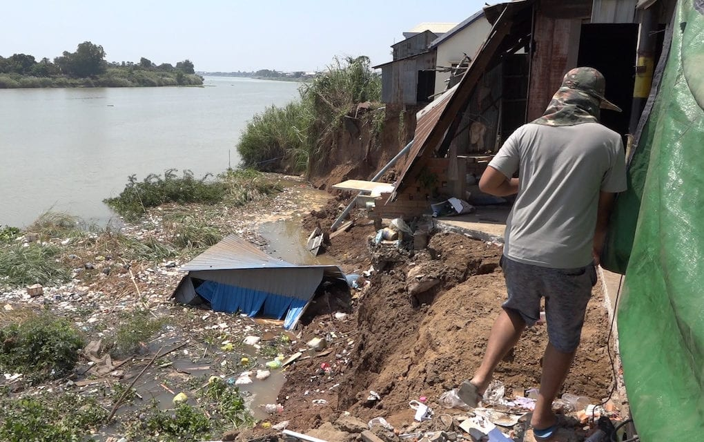 A man walks near a collapsed riverbank and houses along the Bassac river in Takhmao city, Kandal province on February 24, 2020. (Hy Chhay/VOD)