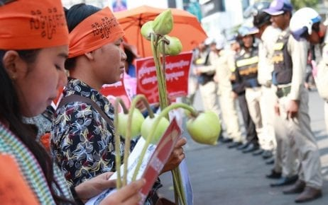 Women hold lotus flowers as authorities look on outside Olympic Stadium in Phnom Penh on March 8, 2019, during a rally marking International Women's Day (Licadho)