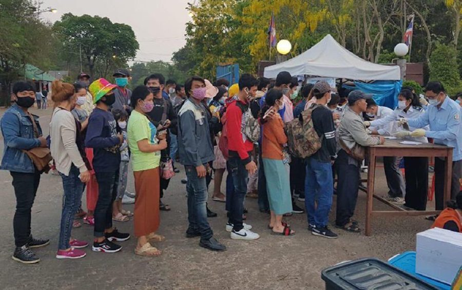 Authorities at the O'Smach International Border Checkpoint check temperatures of Cambodian workers returning from Thailand, in a photograph posted to the Immigration Department's Facebook page on March 23, 2020.