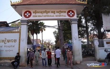 People wearing face masks walk through the gate at the Siem Reap Provincial Hospital on March 26, 2020. (Panha Chorpoan/VOD)