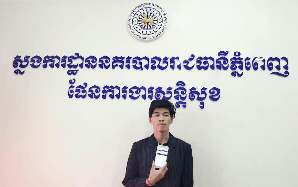 Sovann Rithy, editor of the TVFB news site, holds up a smartphone at the Phnom Penh Municipal Police Headquarters following his arrest on April 7, 2020. (Phnom Penh Municipal Police)
