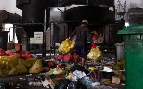 A Medical Waste Management Unit worker navigates the waste-strewn warehouse floor of the Dangkor landfill in Phnom Penh on April 9, 2020. (Gerald Flynn)