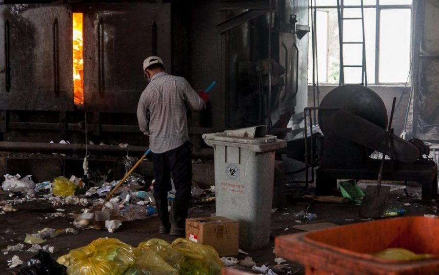 Kimsoam sweeps up medical waste at the Dangkor landfill in Phnom Penh on April 9, 2020. (Gerald Flynn)