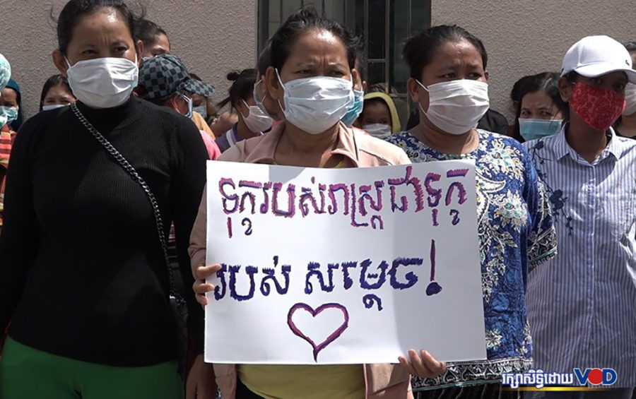 "A woman holds a sign saying ""The pain of the people is the pain of Samdech [Prime Minister Hun Sen]"" as nightlife workers filed a petition to the premier's cabinet asking for aid on June 25, 2020. (Hy Chhay/VOD)"