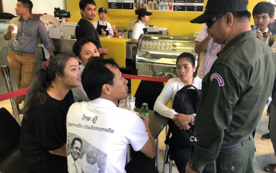 Activists and supporters of slain political analyst Kem Ley speak with a security officer on July 10, 2019, the third anniversary of his death, in the Phnom Penh gas station shop where Kem Ley was killed in 2016. (Matt Surrusco/VOD)