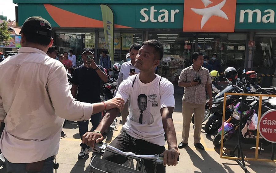 Khan Chanthorn, wearing a T-shirt depicting slain political analyst Kem Ley, is stopped and held by a security officer on July 8, 2020, after Chanthorn had rode his bicycle into the Caltex gas station to commemorate the four-year anniversary of Kem Ley's death at the site where he was killed. (Cambodian Youth Network)