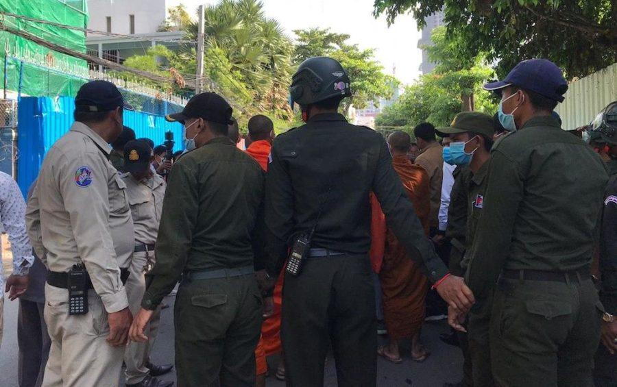 Chamkarmorn district security guards hold hands to block monks and youth activists who attempted to hold a memorial ceremony on July 8, 2020 for slain political activist Kem Ley at the capital's Caltex gas station where he was killed in 2016. (Saut Sok Prathna/VOD)