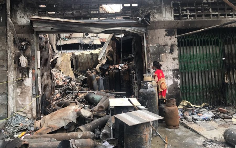 Ly Soeurng stands outside what is left of her family's Phnom Penh gas-refill shop two days after her son, daughter and two workers were killed in a gas explosion and fire on July 18, 2020. (Mech Dara/VOD)