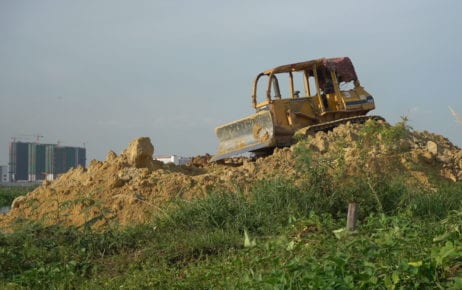 A bulldozer pushing sand and dirt into the wetlands, next to community farms in 2020 near Boeng Choeng Ek (STT)