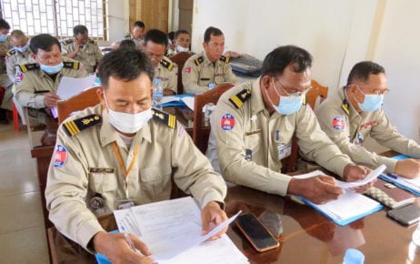 Police officers in Kampong Speu province read documents in this photograph posted to the Immigration Department's Facebook page on July 31, 2020.