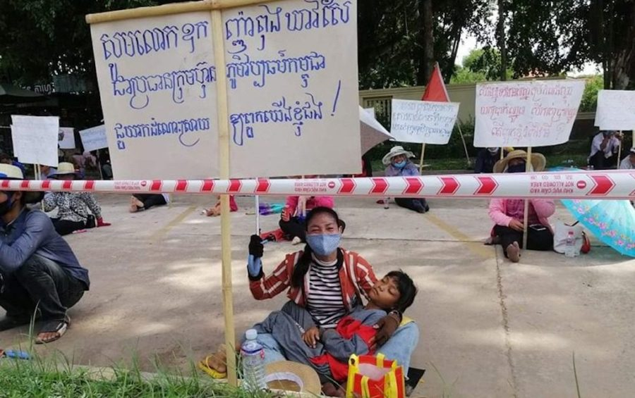 A woman holds a sign during a worker protest at the Cambodian Cultural Village tourism complex in Siem Reap province on August 26, 2020. (Central)