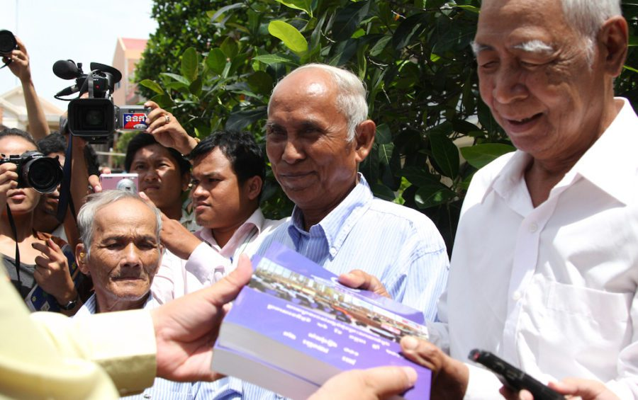 "Bou Meng (left), Chum Mey (center) and Vann Nath (right) after receiving a copy of the verdict against Kaing Guek Eav, known as ""Duch,"" on August 12, 2010. They are three of only a handful of survivors of the Khmer Rouge prison S-21, where more than 10,000 people were tortured and executed. (ECCC)"