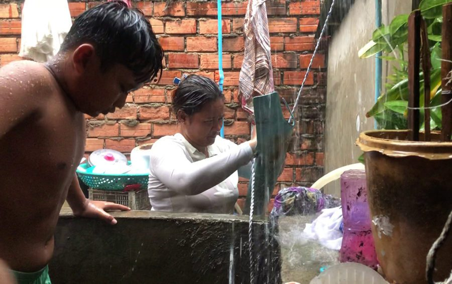 A family collects rainwater to save money on water expenses, in Phnom Penh's Chbar Ampov district on June 12, 2020. (Hun Sirivadh/VOD)
