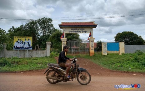 A man rides a motorbike in front of Bosra commune's Sreu Kleng primary school in Mondulkiri province on August 13, 2020 (Uy Sothea/VOD)