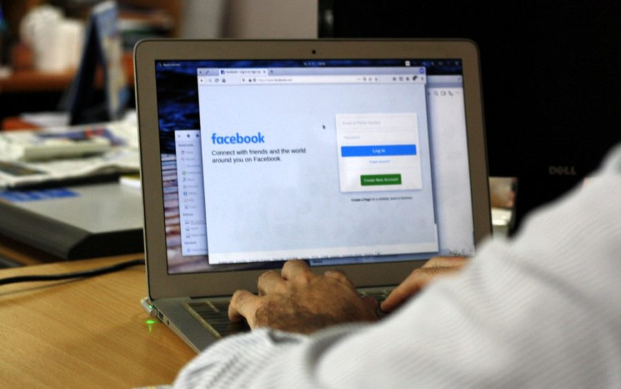 man types on laptop with screen showing Facebook login