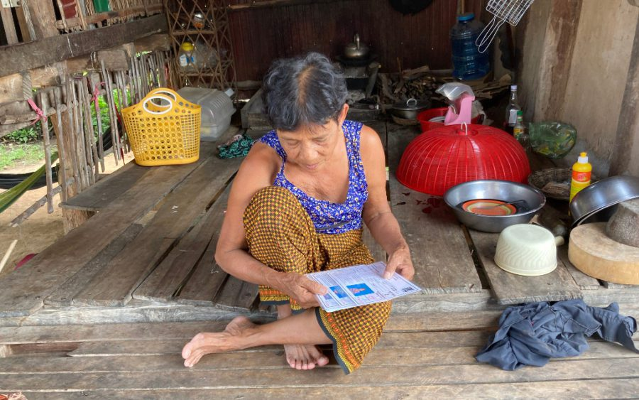 Preh Phnheas resident Chorb Kun looks at her IDPoor and loan documents last month in Battambang province. (Ananth Baliga/VOD)