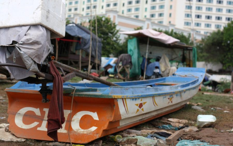 A fishing boat sits on the shore of Phnom Penh's Chroy Changva with the Sokha Hotel in the background, on September 15, 2020. (Michael Dickison/VOD)