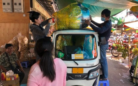 An O'Russei Market vendor and a tuk-tuk driver fasten Chhim Savoeurn's Pchum Ben offerings package to the top of a vehicle on September 15, 2020. (Matt Surrusco/VOD)