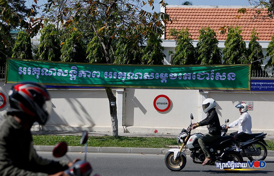 "Motorbike drivers pass a sign saying ""Thank you for the peace, thank you Samdech Techo Hun Sen"" at the Anti-Corruption Unit in Phnom Penh on January 2, 2020. (Panha Chorpoan/VOD)"