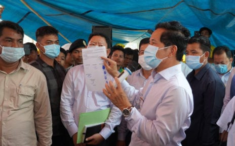 Phnom Penh governor Khuong Sreng holds up City Hall's offer to guarantee striking garbage collectors' benefits will not be lost amid restructuring, at Cintri's truck garage in Daun Penh district on October 7, 2020. (Tran Techseng/VOD)