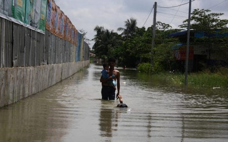 Lu Veasna, 32, carries his child through floodwaters in Phnom Penh's Dangkao district on October 12, 2020. (Michael Dickison/VOD)