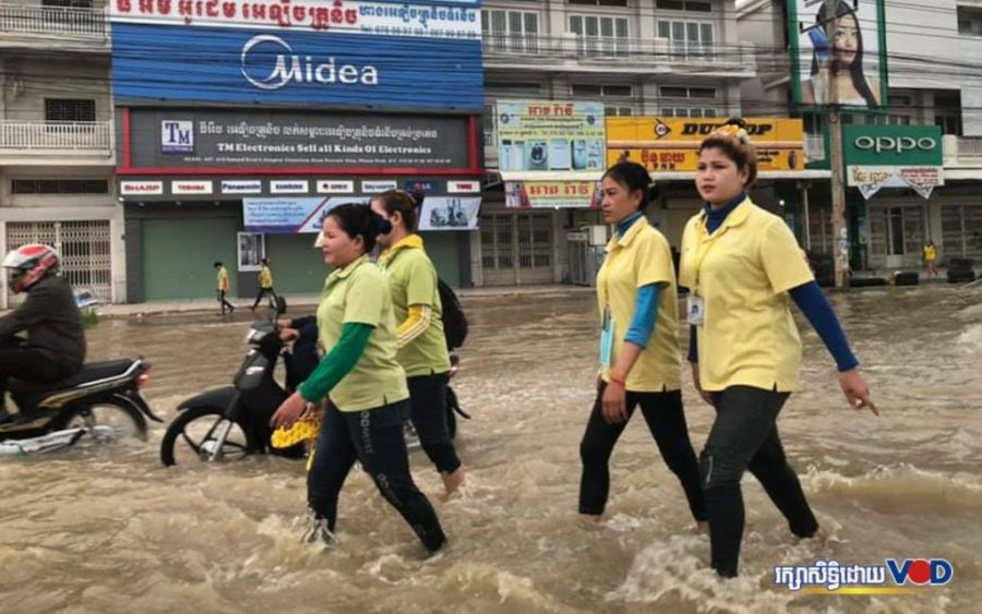 Workers wade through a flooded street in Phnom Penh on October 13, 2020. (Heng Vichet/VOD)