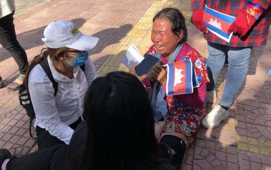 Demonstrator Sath Pha sits on the ground crying after being carried away from the Chinese Embassy in Phnom Penh by security guards following a protest across the street on October 23, 2020 (Matt Surrusco/VOD)