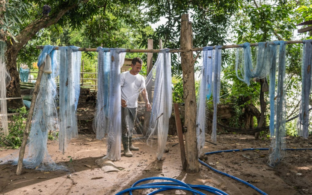 O'Svay commune former fisheries chief Kong Chanthy checks fishing nets hanging near his family's restaurant and dock in Stung Treng province on August 14, 2020. (Enric Català/VOD)
