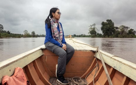 Chea Seila, a social researcher who focuses on communities in the Stung Treng province's Ramsar protected wetlands, rides a boat on the Mekong River on August 13, 2020. (Enric Català/VOD)