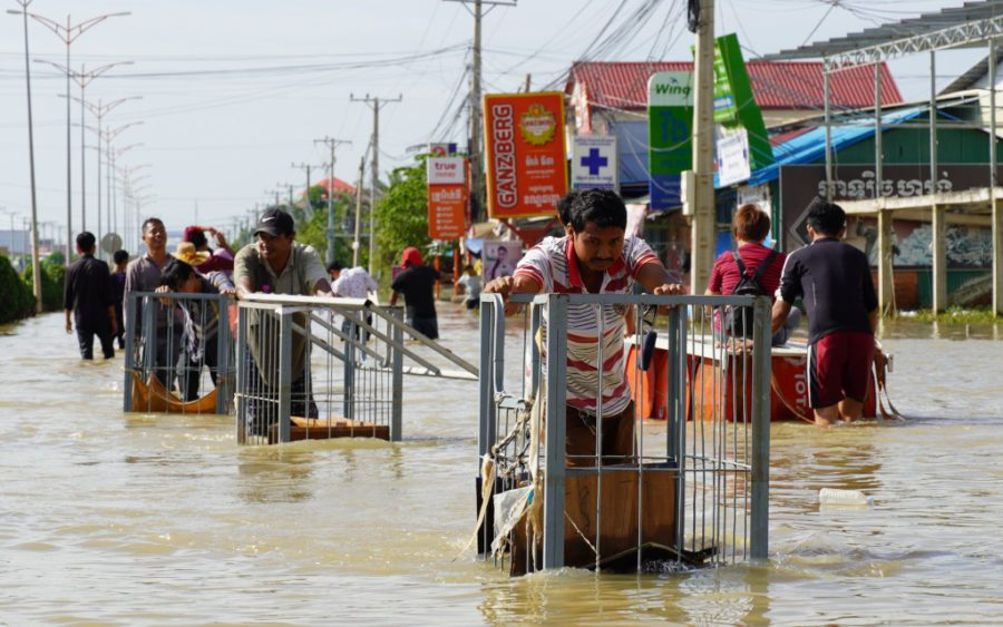 Workers roll a garment factory's carts through floodwaters in Phnom Penh's Dangkao district on October 22, 2020. (Tran Techseng/VOD)