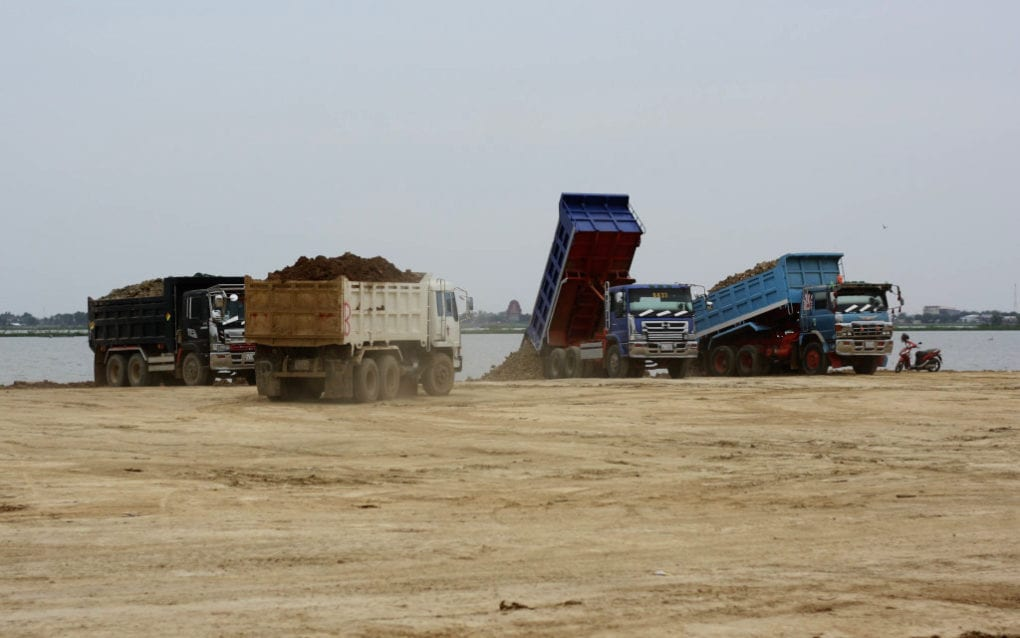Trucks dump dirt as they fill in land at Phnom Penh's Boeng Tamok lake, on October 28, 2020. (Michael Dickison/VOD)