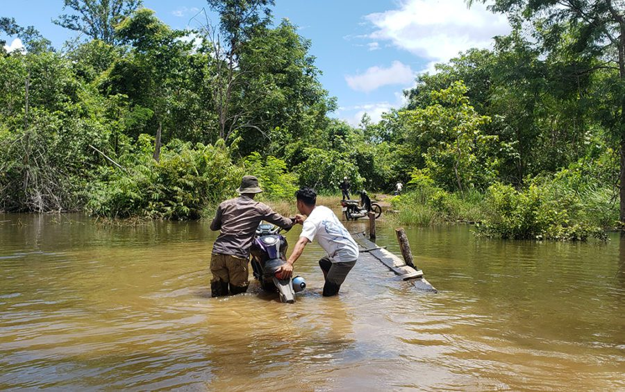 Residents of Old Kbal Romeas pull their motorbikes through flooded waters to reach their ancestral land in Stung Treng province on September 22, 2020. (Danielle Keeton-Olsen/VOD)