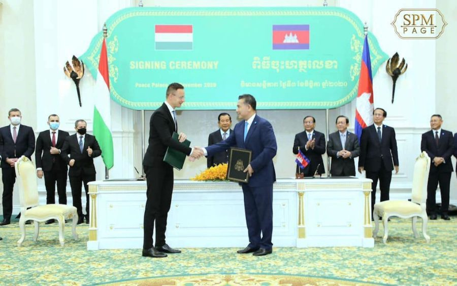 Hungarian Foreign Minister Peter Szijjarto shakes hands with Minister in Charge of Civil Aviation Mao Havannall at a signing ceremony in Phnom Penh on November 3, 2020, as Prime Minister Hun Sen and other officials look on, in this photograph posted to Hun Sen's Facebook page.