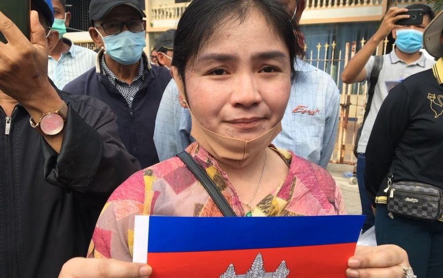 Sin Chanpeou Rozeth, a former CNRP commune chief in Battambang province, holds up a small Cambodian flag outside the Phnom Penh Municipal Court on November 26, 2020.