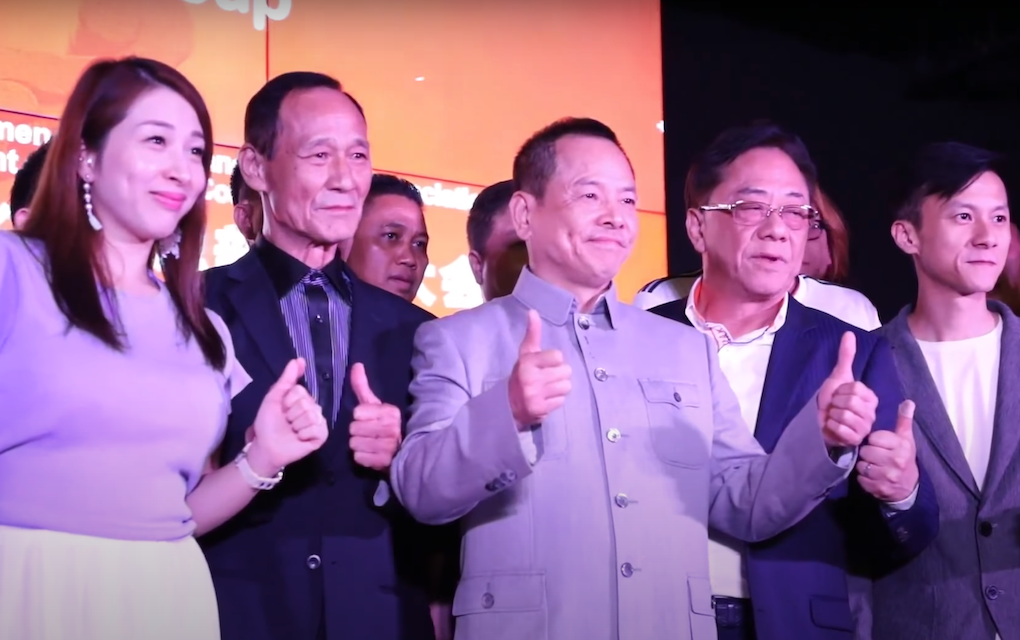 """Former Macau crime boss Wan Kuok Koi, also known as """"Broken Tooth,"""" (center) at a ceremony in Kuala Lumpur in July 2018 marking the establishment of the World Hongmen History and Culture Association headquarters, in a screenshot from a promotional video."""