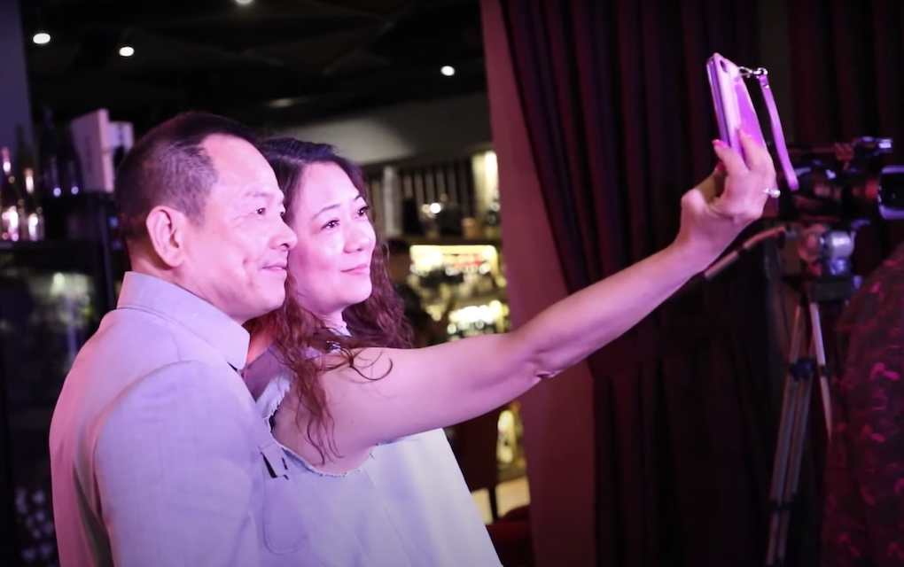 """Former Macau crime boss Wan Kuok Koi, also known as """"Broken Tooth,"""" takes a selfie with a woman at a ceremony in Kuala Lumpur in July 2018 marking the establishment of the World Hongmen History and Culture Association headquarters, in a screenshot from a promotional video."""