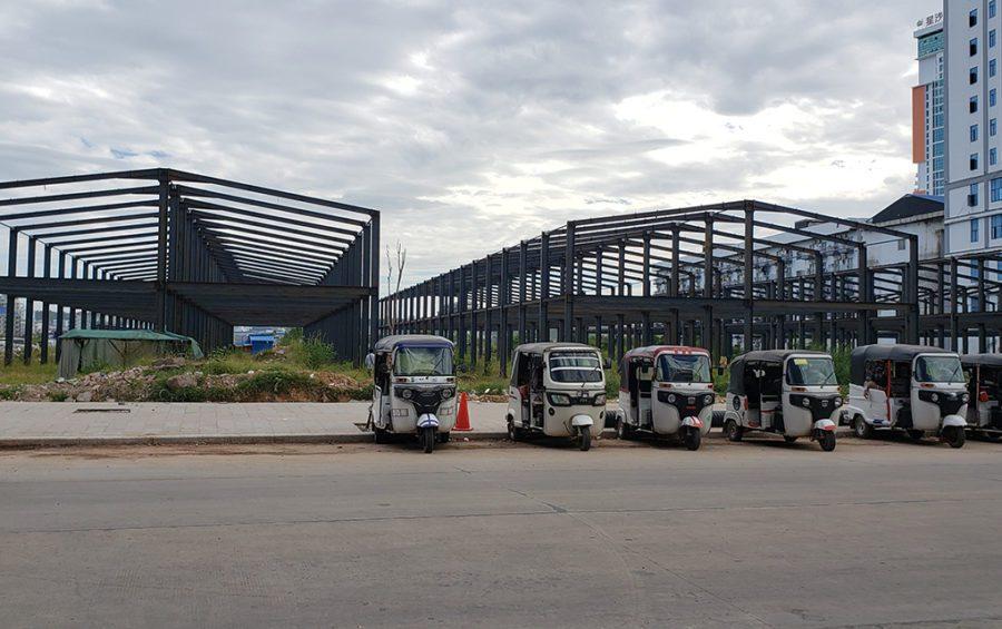 A row of tuk tuks park in front of building frames in Sihanoukville on December 2, 2020. (Danielle Keeton-Olsen/VOD)