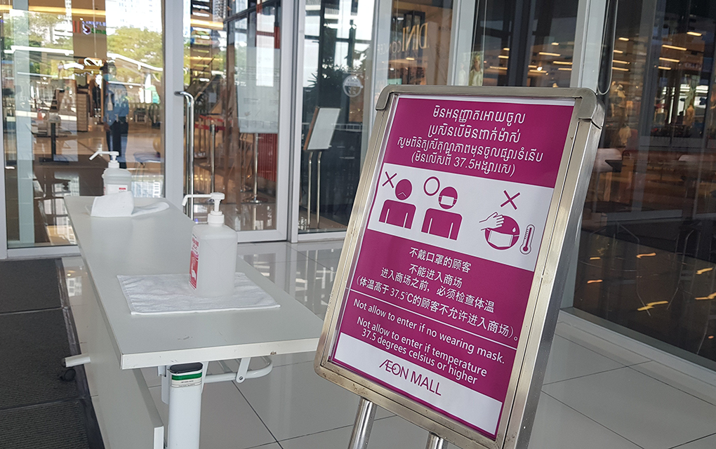 A sign requiring Aeon Mall 1 customers to wear a mask and take a temperature check, placed at the entrance of the building in Phnom Penh's Chamkarmon district on December 4, 2020. (Tran Techseng/VOD)