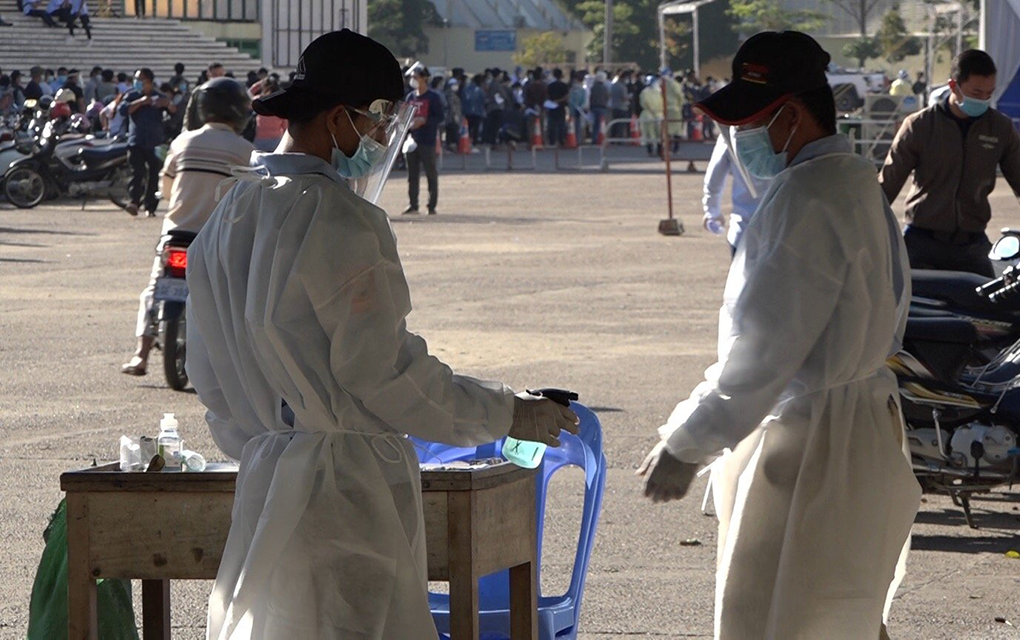 A health worker sprays alcohol sanitizer on a colleague at the Covid-19 testing center at Olympic Stadium in Phnom Penh on December 8, 2020. (Hy Chhay/VOD)