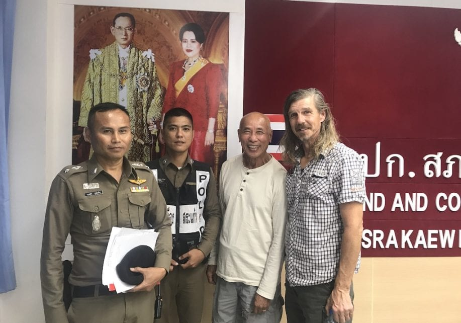 Cambodian-American CNRP supporter Hay Kimsan (second right) and American Daniel Capka pose with Thai police officers at Sa Kaeo police station on November 8, 2019. (Supplied)