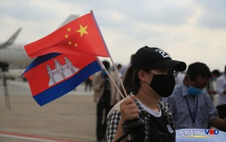 A woman waves the Cambodian and Chinese flags at the Phnom Penh International Airport on March 23, 2020. (Chorn Chanren/VOD)